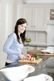 Woman preparing a meal in the kitchen. Beautiful young woman preparing the ingredients for a meal in her kitchen Stock Photo