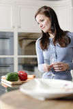 Woman preparing a meal in the kitchen Stock Photos