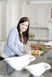 Woman preparing a meal in the kitchen. Beautiful young woman preparing the ingredients for a meal in her kitchen Stock Images
