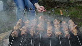 Woman preparing meat. Woman hand turn bake fresh natural chicken meat shashlik on steel spit and smoke rise stock video