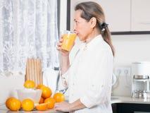 Woman drinking orange juice. Woman preparing orange juice in kitchen stock photography
