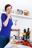Woman preparing pasta dish and talking on the phone. Young woman in her kitchen preparing a pasta dish and talking on the phone Stock Photography