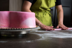 Woman preparing pink fondant for cake decorating, focus on the cake Stock Images