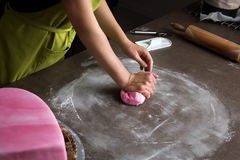 Woman preparing pink fondant for cake decorating, hands detail. Unrecognisable woman preparing pink fondant for cake decorating, hands detail royalty free stock photo