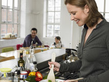 Woman Preparing Salad With Family Sitting In Background At Home Royalty Free Stock Image