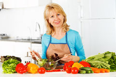 Woman preparing salad in the kitchen. Royalty Free Stock Photography