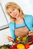 Woman preparing salad in the kitchen Royalty Free Stock Photo