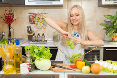 Woman preparing salad at the kitchen table Royalty Free Stock Images