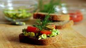 Woman preparing sandwich with avocado, tomato and olives. 4k close up.  stock video