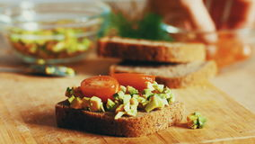 Woman preparing sandwich with avocado, tomato and olives. 4k close up. Graded.  stock video