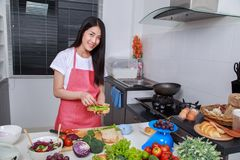 Woman preparing a sandwich in kitchen room stock images