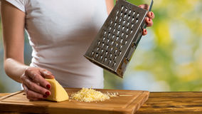Woman preparing sauce for pasta and grating cheese Stock Photos