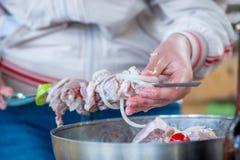 Woman preparing shish kebab, close-up of hands, skewer Royalty Free Stock Photo
