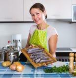 Woman preparing small fish indoors. Portrait of adult girl preparing small fish indoors royalty free stock photo