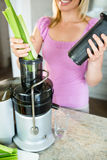 Woman preparing a smoothie in the kitchen Royalty Free Stock Photography