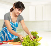 Woman preparing some heathy food. Young smiling woman in the kitchen preparing some heathy food for dinner stock images
