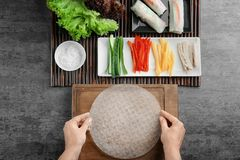 Woman preparing spring rolls in rice paper. On kitchen table Royalty Free Stock Images