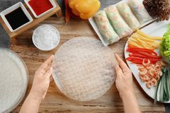Woman preparing spring rolls in rice paper. On kitchen table Royalty Free Stock Photography