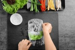Woman preparing spring rolls in rice paper. On kitchen table Royalty Free Stock Photos