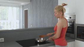 Woman preparing at the stove. Pan with finely chopped onions. Woman stirs a wooden spatula frying onions. stock video