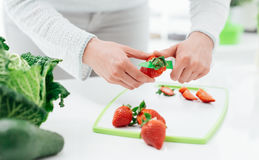 Woman preparing strawberries. Woman preparing a snack in her kitchen, she is cutting some fresh tasty strawberries on a chopping board Royalty Free Stock Image