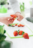 Woman preparing strawberries. Woman preparing a snack in her kitchen, she is cutting some fresh tasty strawberries on a chopping board Royalty Free Stock Photos
