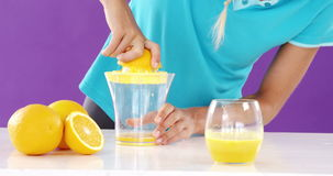Woman preparing sweet lime juice from juicer against violet background. Beautiful woman preparing sweet lime juice from juicer against violet background stock footage