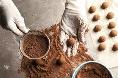 Woman preparing tasty chocolate truffles at table. Top view royalty free stock images