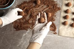 Woman preparing tasty chocolate truffles at table. Top view royalty free stock photography