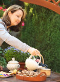 Woman preparing tea in teapot in a garden Royalty Free Stock Images