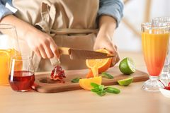 Woman preparing Tequila Sunrise cocktail. In kitchen stock image
