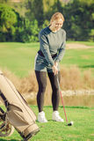 Woman preparing to hit ball at golf course Royalty Free Stock Photos