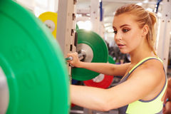 Woman preparing to lift barbells at a squat rack in a gym Royalty Free Stock Photography