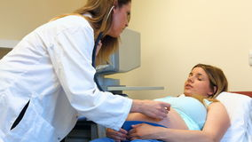 Woman preparing from ultrasound. While doctors rubs her stomach stock footage