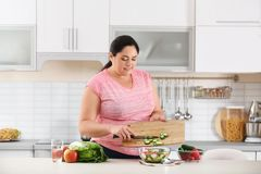 Woman preparing vegetable salad on table in kitchen royalty free stock image
