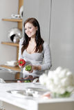 Woman preparing vegetables. Beautiful young woman preparing food in her modern kitchen at home Stock Photography