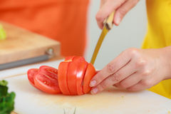Woman preparing vegetables salad slicing tomato Royalty Free Stock Images