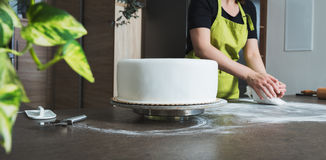 woman preparing white fondant for cake decorating, hands detail, focus on the cake Royalty Free Stock Photography