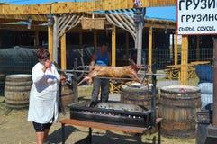 Woman preparing whole lamb on BBQ at national Ukrainian annual market `Sorochinska. Velyki Sorochintsi, UKRAINE - AUGUST 25, 2017: Woman preparing whole lamb on Royalty Free Stock Photo