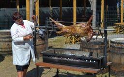 Woman preparing whole lamb on BBQ at national Ukrainian annual market `Sorochinska. Velyki Sorochintsi, UKRAINE - AUGUST 25, 2017: Woman preparing whole lamb on Stock Photography