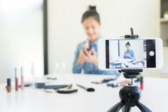 Woman present beauty product and broadcast live video to social Stock Photos