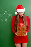 Woman with present, wearing santa hat. Royalty Free Stock Photos