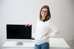 Woman presenting blank monitor screen Royalty Free Stock Photography