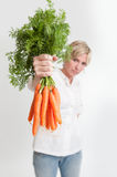 Woman presenting a bunch of carrots Stock Photography
