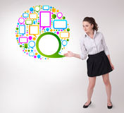 Woman presenting colourful speach bubble. Young business woman presenting colourful speach bubble on bright background Royalty Free Stock Photography