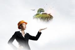 Woman presenting construction model . Mixed media Stock Image