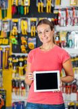 Woman Presenting Digital Tablet In Hardware Shop Royalty Free Stock Image