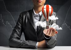 Woman presenting flying balloon in hand. Royalty Free Stock Photo