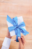 Woman presenting gift with blue ribbon Stock Photo