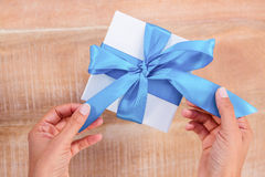 Woman presenting gift with blue ribbon Stock Photography